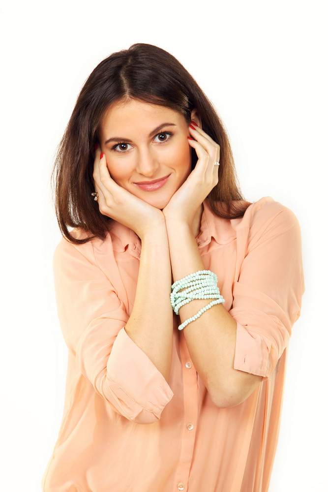 Charming and joyful woman with pearl bracelet posing in a studio