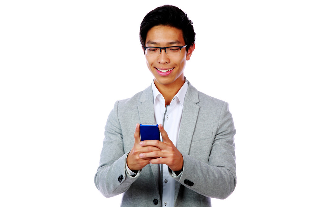 Cheerful asian man using smartphone over white background