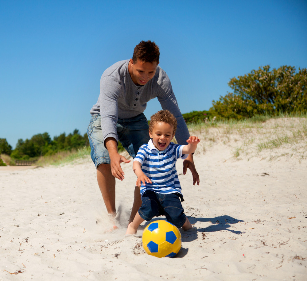 Cheerful boy together with his dad chases the ball outdoors