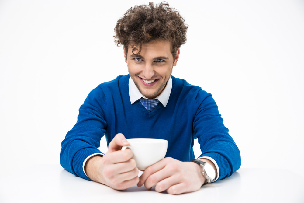 Cheerful business man sitting at the table with cup of coffee