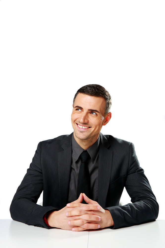 Cheerful businessman sitting at the table and looking away isolated on a white background