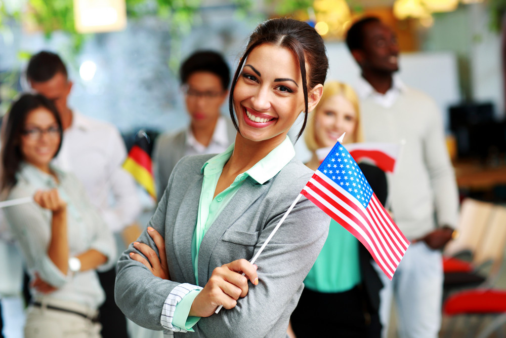 Cheerful businesswoman holding flag of USA in front of colleagues