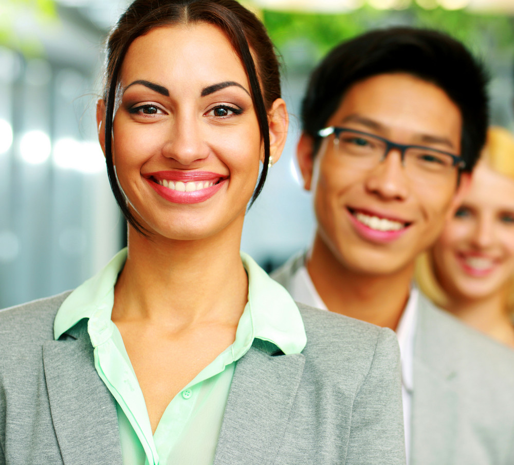 Cheerful businesswoman standing in front of colleagues