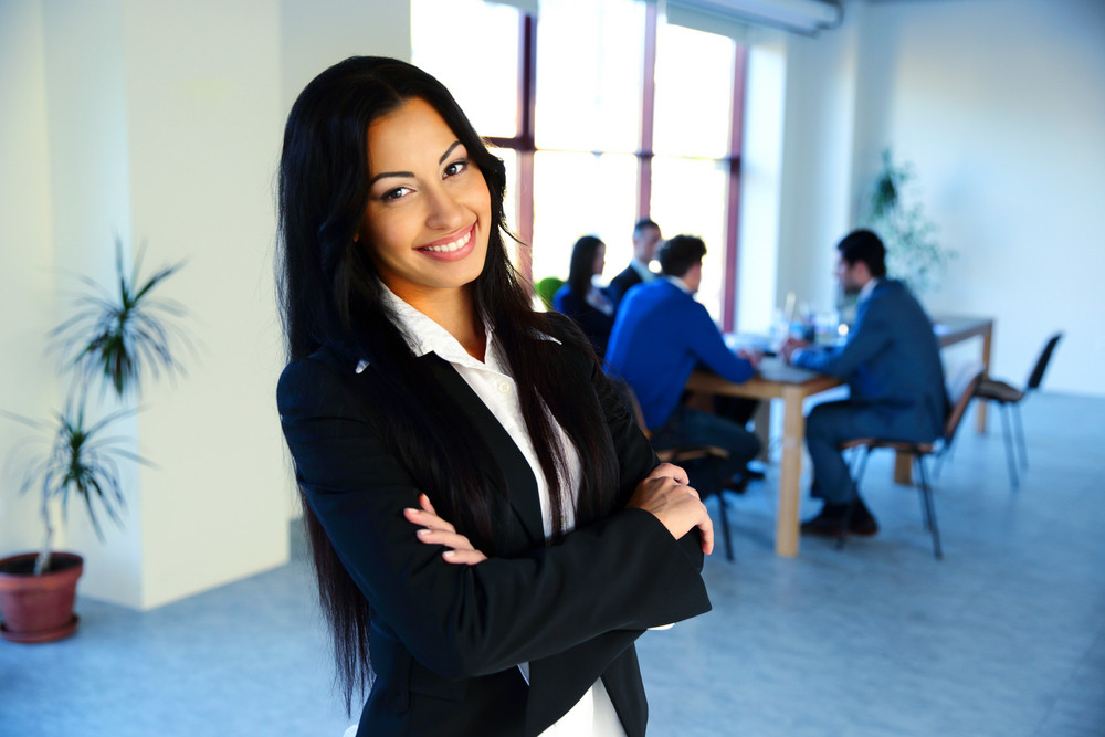 Cheerful businesswoman standing with arms folded in front of colleagues