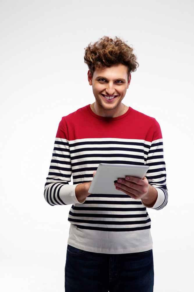 Cheerful casual man using tablet computer over gray background
