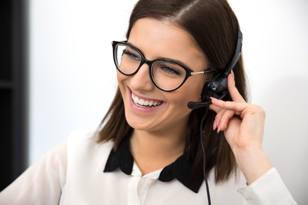 Cheerful female support operator in headset
