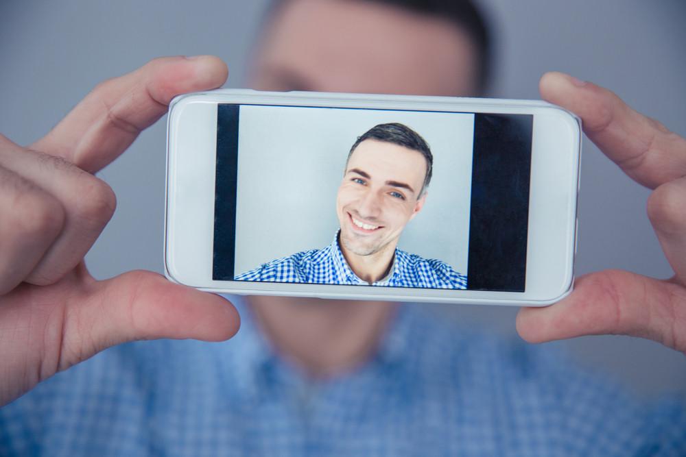 Cheerful man making selfie photo