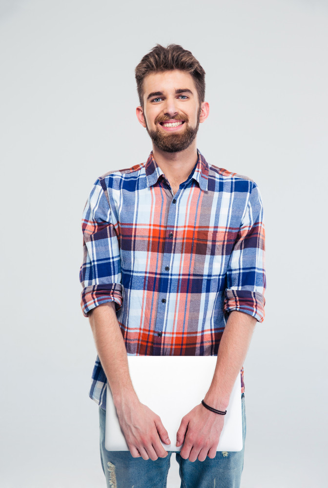 Cheerful man standing and holding laptop