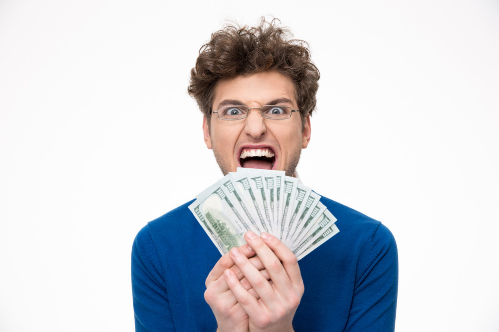Cheerful man with glasses holding money over white background