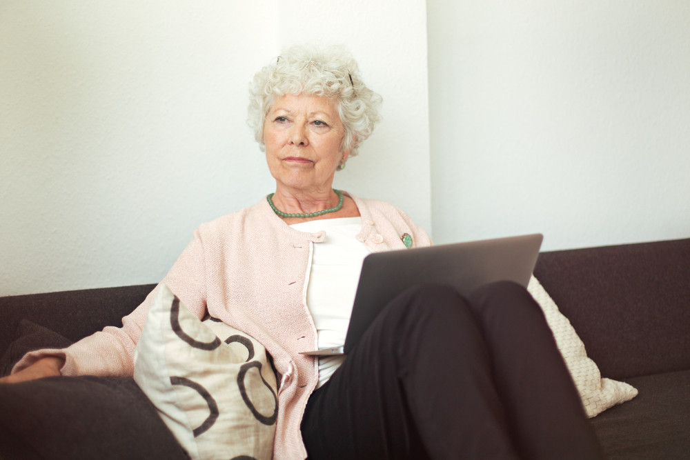 Cheerful senior lady smelling a flower indoors