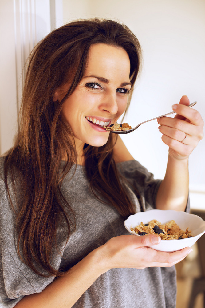 Cheerful Woman Holding a Bowl of Cereal