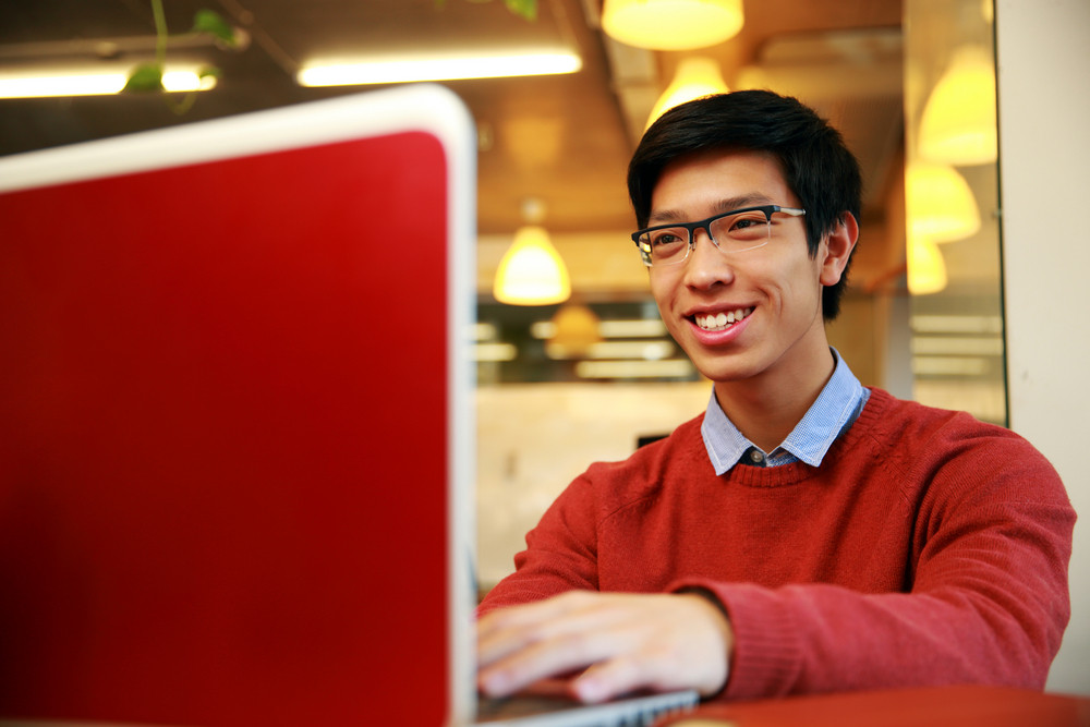 Cheerful young asian man using laptop