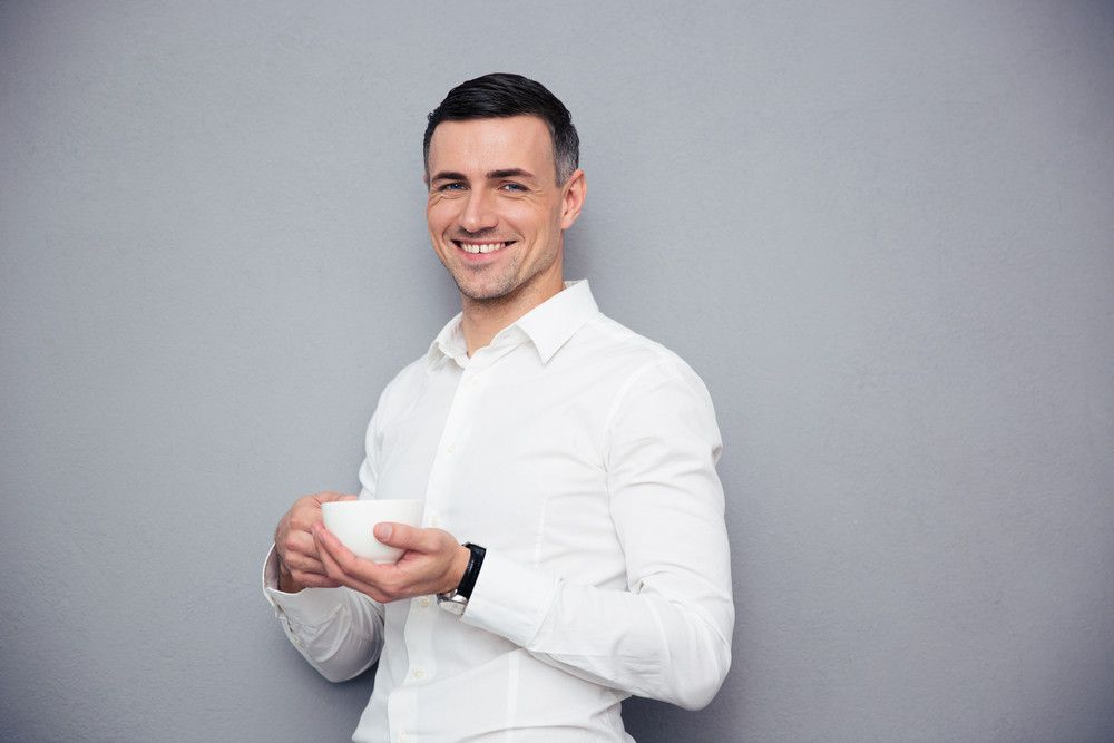 Cheerful young businessman holding cup of coffee