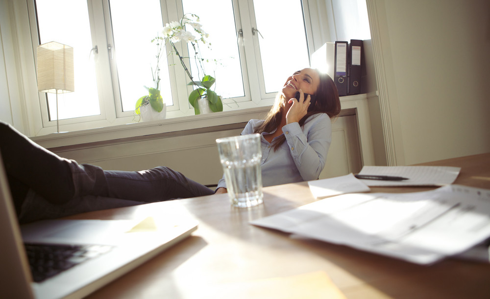 Cheerful young businesswoman sitting at her desk with legs on table talking on mobile phone. Caucasian young female relaxing in home office.