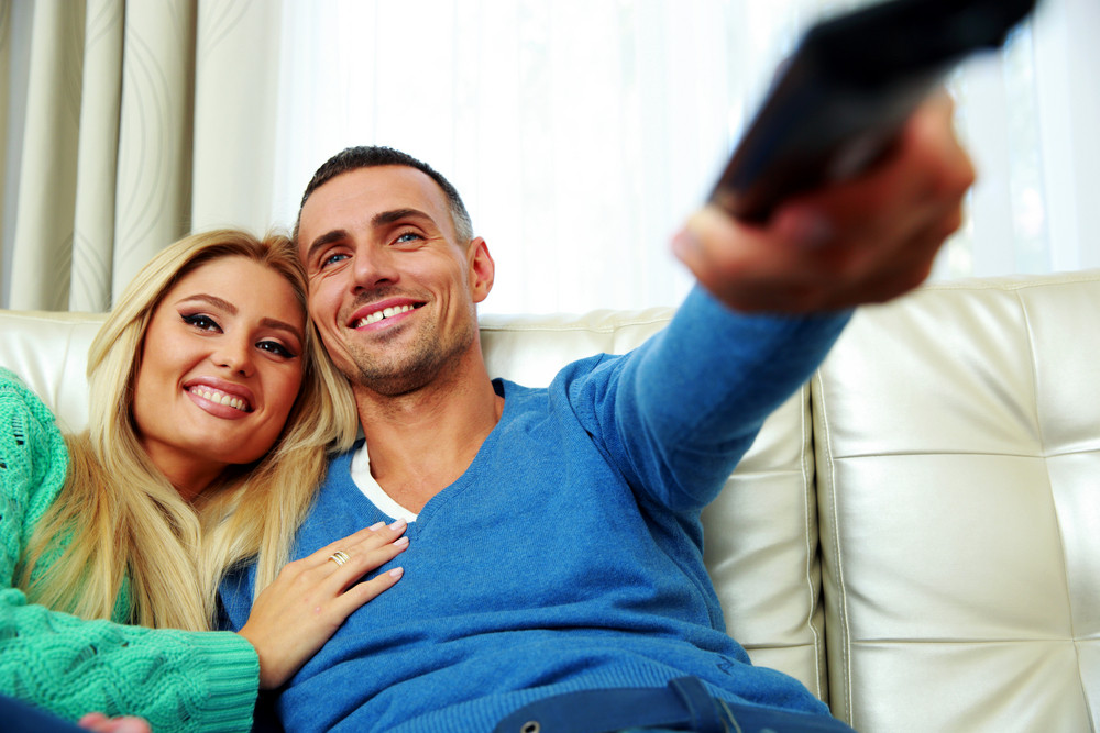 Cheerful young couple sitting on the sofa and watching TV
