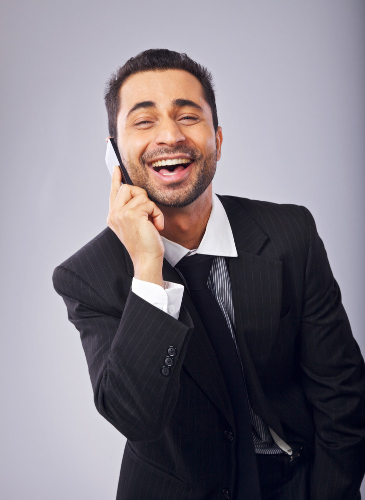 Cheerful young professional laughing while answering a phone call
