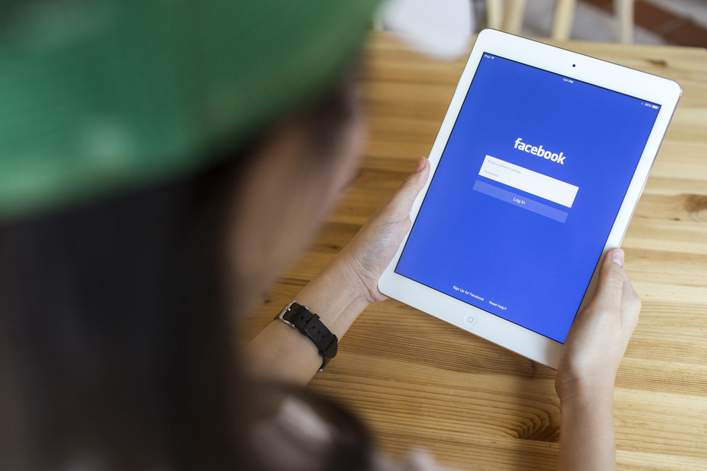 CHIANG MAI, THAILAND - SEPTEMBER 07, 2014: A girl trying to log in Facebook application using Apple iPad Air. Facebook is largest and most popular social networking site in the world.