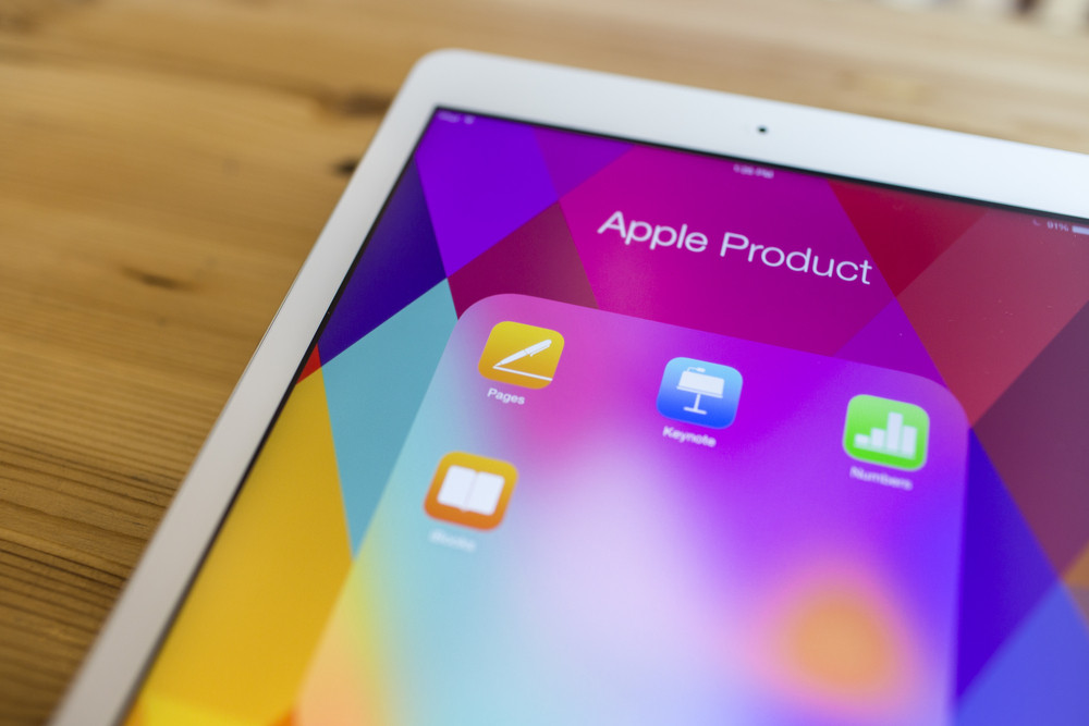Popular Apple productivity apps icons shown on an Apple iPad Air device screen on a wood background.