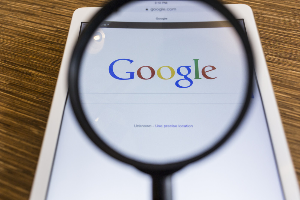 CHIANG MAI, THAILAND - SEPTEMBER 17, 2014: Magnifying glass of Google search page view on web browser Apple iPad Air device.