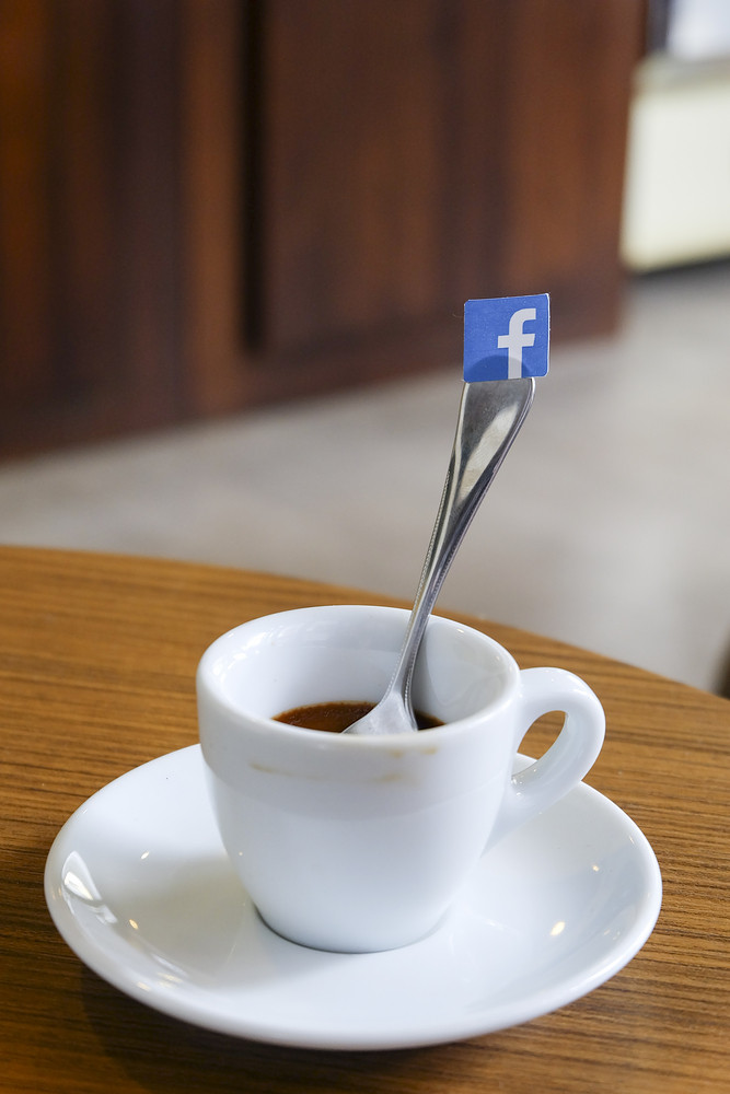 CHIANG MAI, THAILAND - SEPTEMBER 24, 2014: Facebook social media brands printed on sticker and placed on coffee spoon wood table.