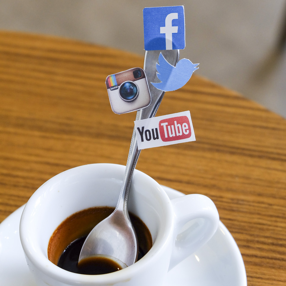 CHIANG MAI, THAILAND - SEPTEMBER 24, 2014: Social media brands printed on sticker and placed on coffee spoon wood table. Include Facebook, Twitter, Instagram and Youtube.