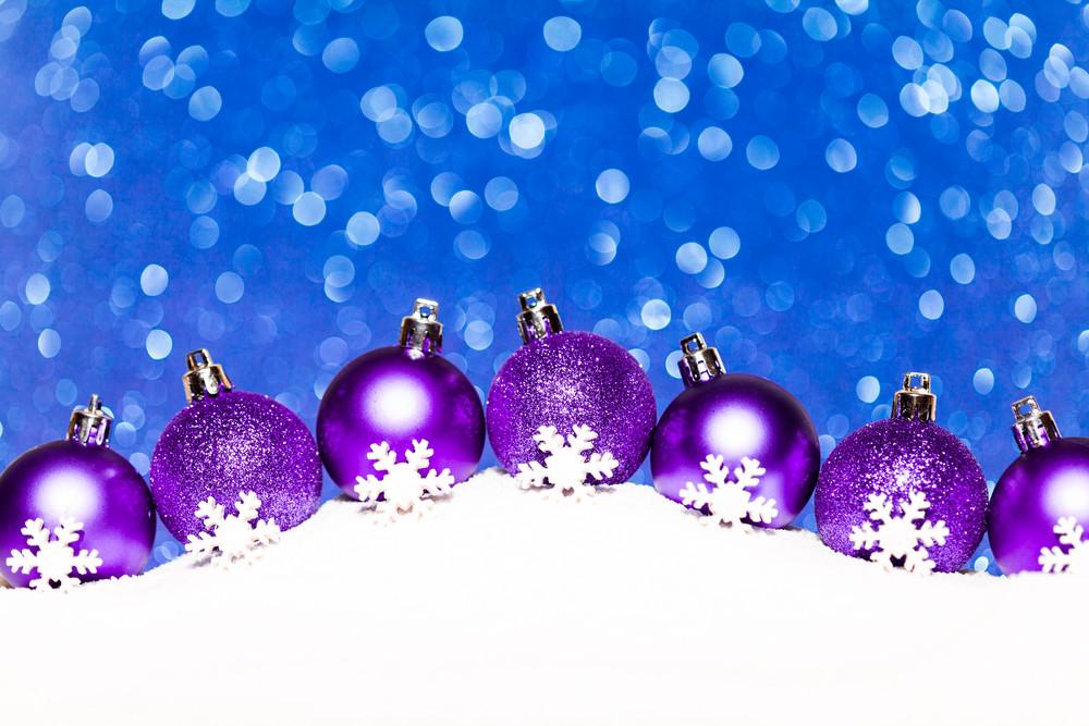 Christmas purple balls in snow on blue glitter background