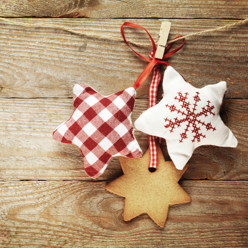 Gingerbread cookies and christmas decorations hanging over wooden background