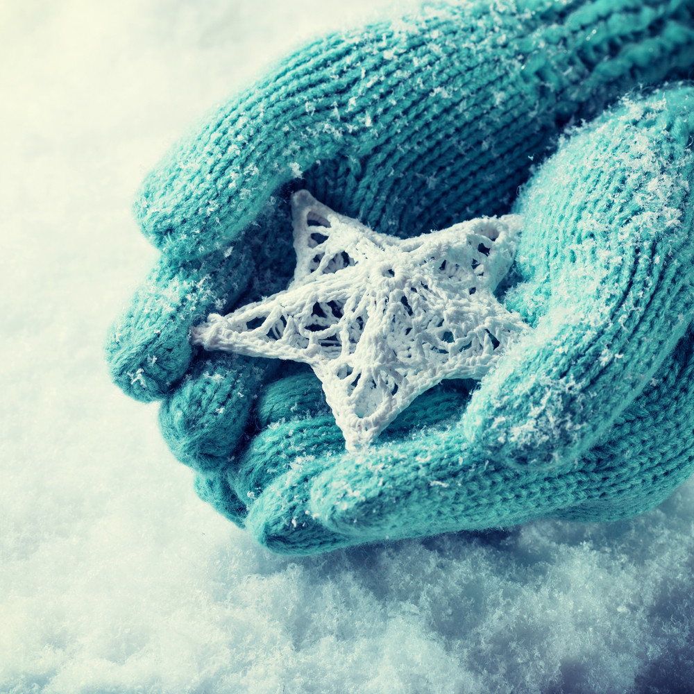 Blue gloved hands holding snowflake