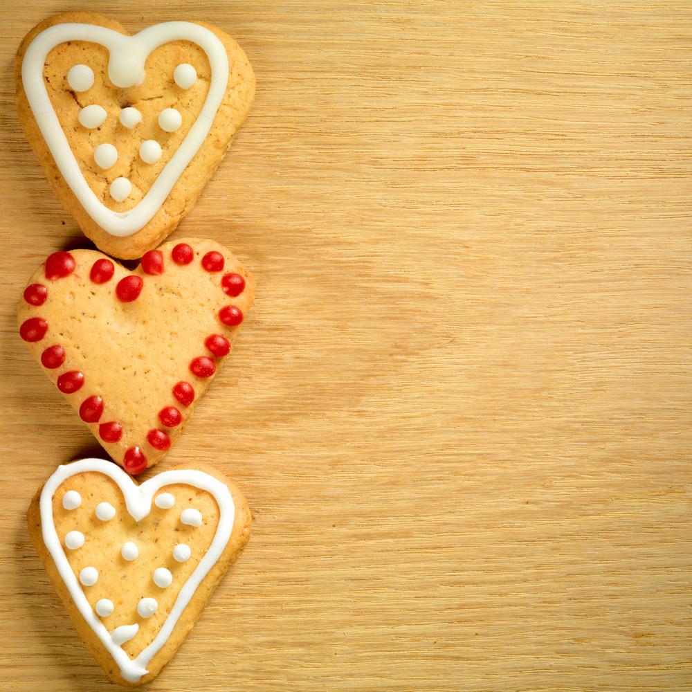 Gingerbread cookies hanging over wooden background