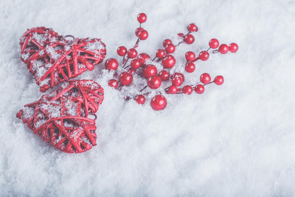 兩個美麗浪漫的復古紅色的心在白色的雪的冬天背景槲寄生漿果。聖誕