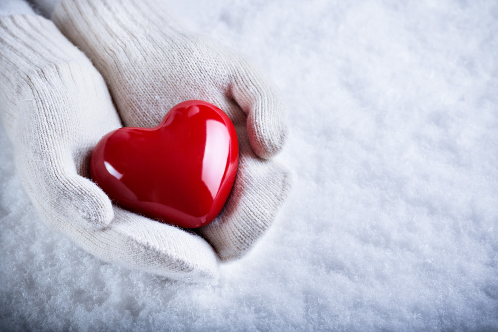 Female hands in white knitted mittens with a glossy red heart on a snow background.