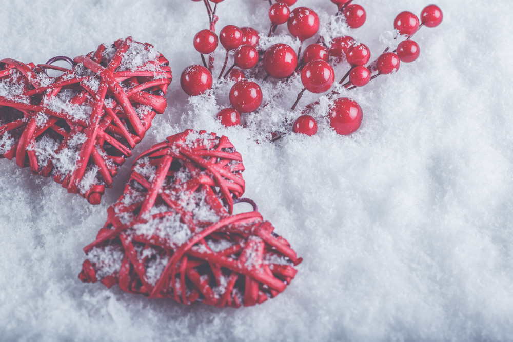 Two beautiful romantic vintage red hearts with mistletoe berries on a white snow winter background. Christmas