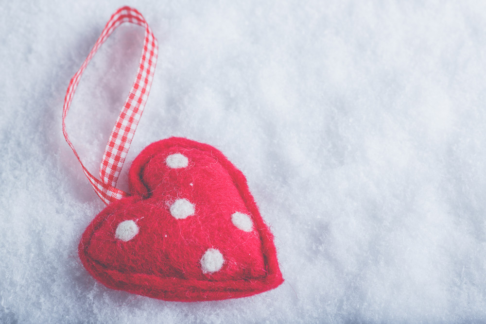 Red toy suave heart on a frosty white snow winter background.