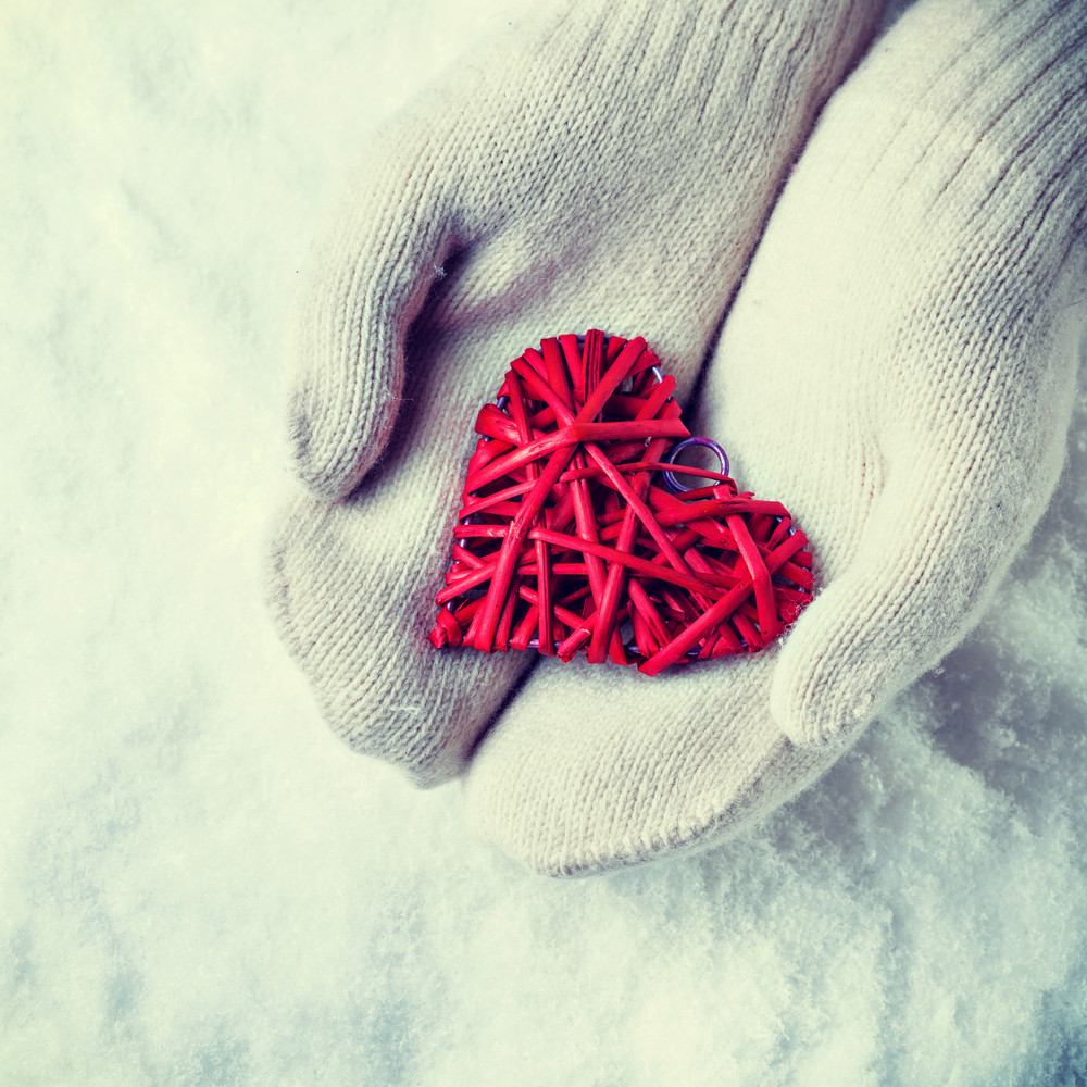 Female hands in white knitted mittens with a entwined vintage romantic red heart on a snow background.