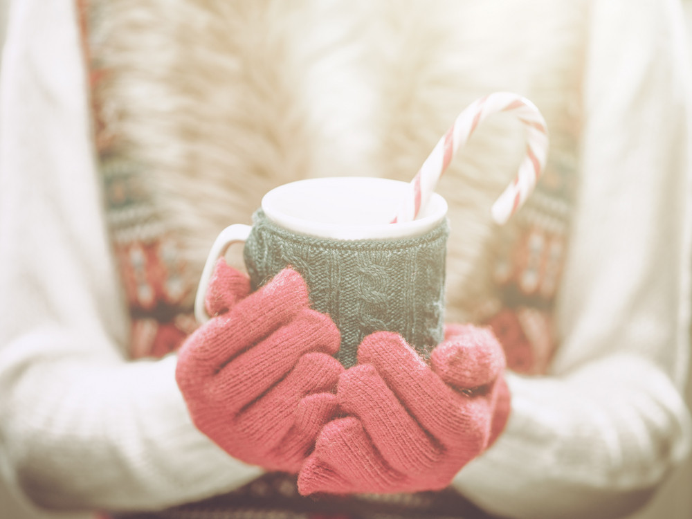 Woman holding winter cup close up on light background. Woman hands in woolen red gloves holding a cozy mug with hot cocoa