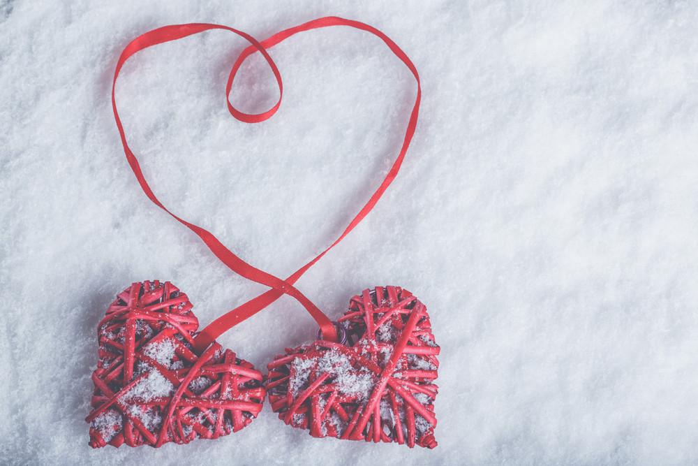 Zwei schöne romantische Vintage roten Herzen gebunden zusammen mit einem Band auf einem weißen Schnee Winter Hintergrund. Liebe und Valentinstag-Konzept.