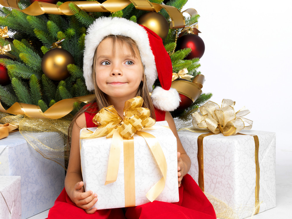 Pretty little girl smiling with present near the Cristmas tree