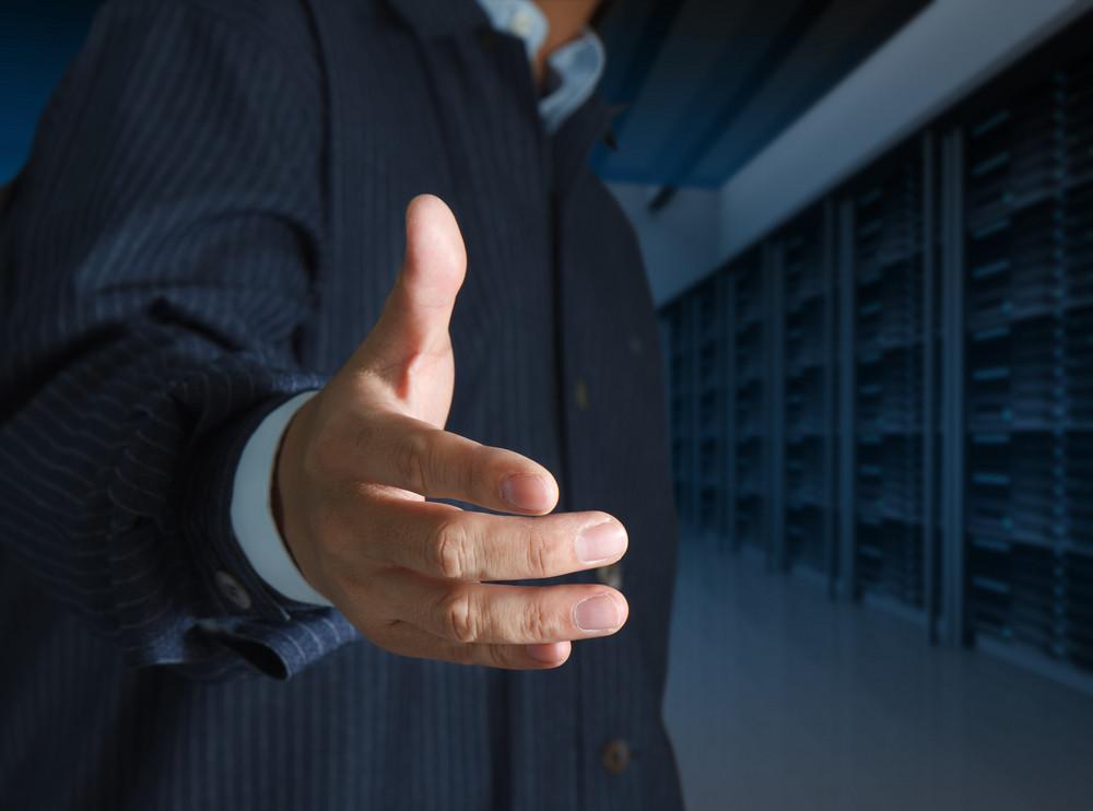 Close Up Businessmen Offer Hand Shake In A Technology Data Center
