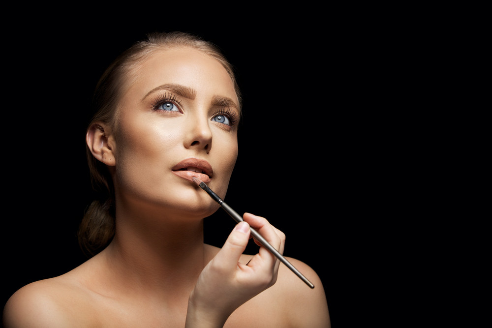 Close up image of attractive young female model applying lip gloss looking up. Beautiful caucasian woman applying make up against black background
