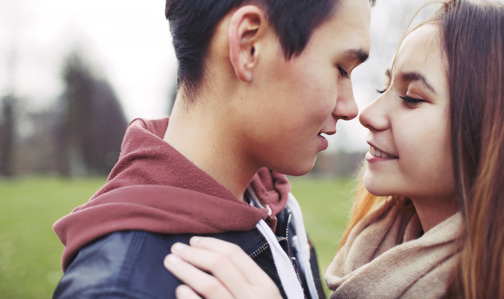 Close up image of romantic young couple in park. Asian teenage couple about to kiss each other while outdoors on a date.