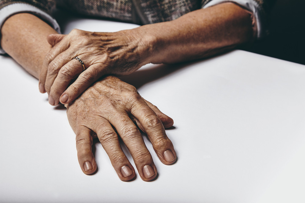 Close-up image of senior woman sitting by a table with focus on her hands. Old female hands on a desk.