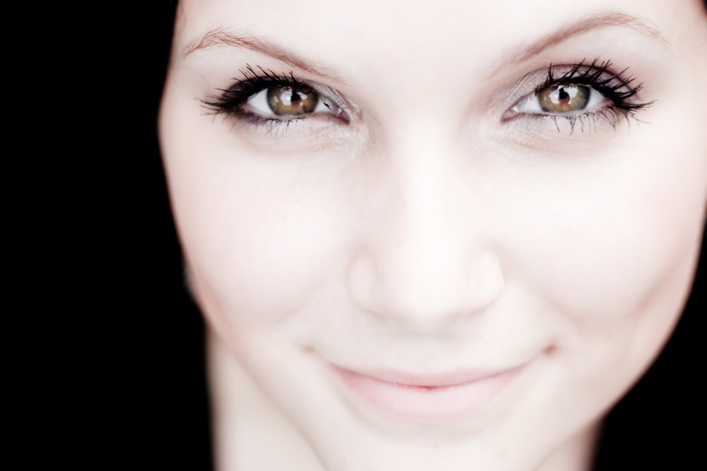 Close up of a beautiful young womans pretty face with copy space in sepia tone.  Shallow depth of field with sharpest focus on the eyes.