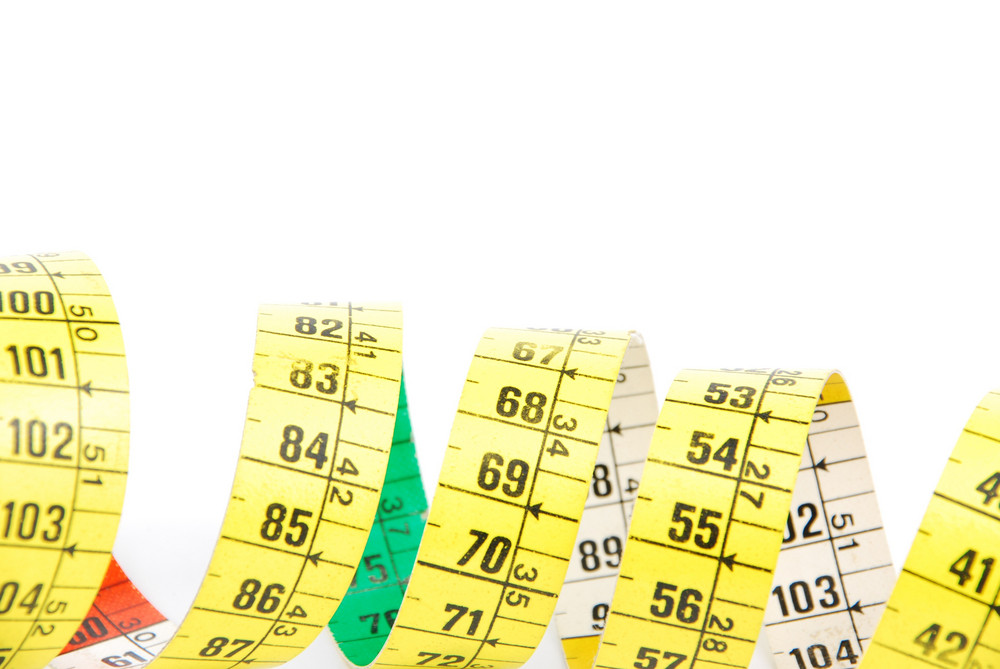 Close-up Of A Curled Measuring Tape On White