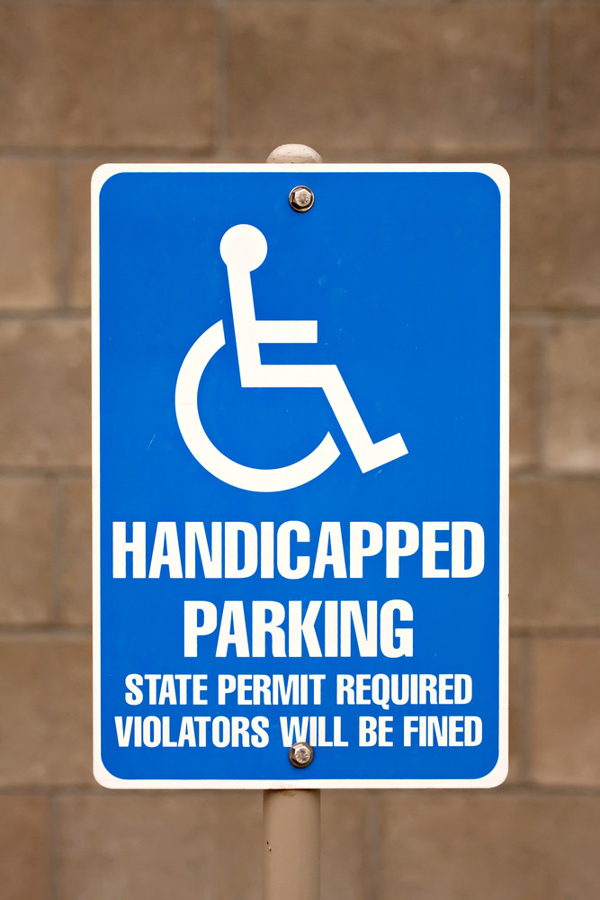 Close up of a handicapped parking sign posted in a parking lot.
