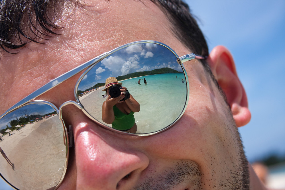 Close up of a man wearing reflective sunglasses in a tropical beach with reflection of the female photographer in the lens. Shallow depth of field.