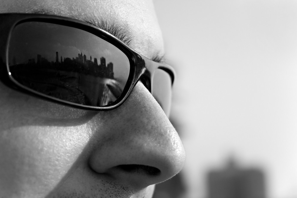 Close up of a man wearing sunglasses with the New York City skyline reflecting in the lens. Shallow depth of field.