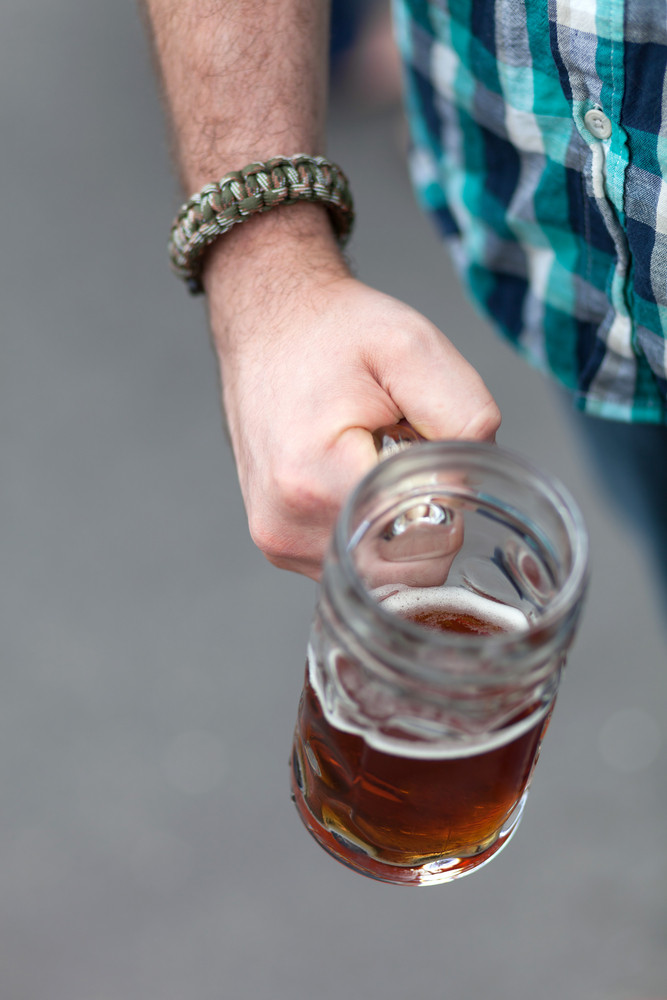Close up of a mans hand holding a stein of beer for Octoberfest.  Shallow depth of field.