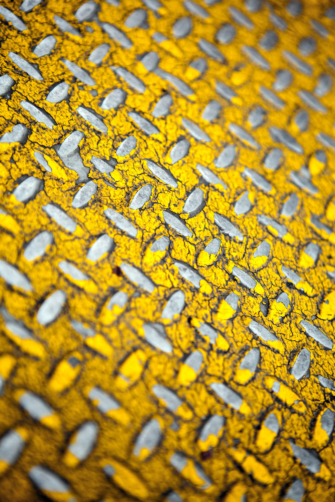 Close up of real diamond plate material.  Most of the yellow paint is chipped and scratched off. Shallow depth of field.