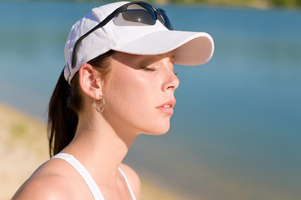 Close-up of summer active woman with cap enjoying sun