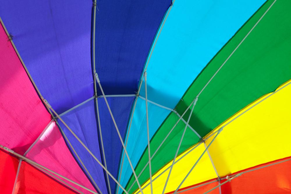 Close up of the interior of a rainbow colored rain umbrella.